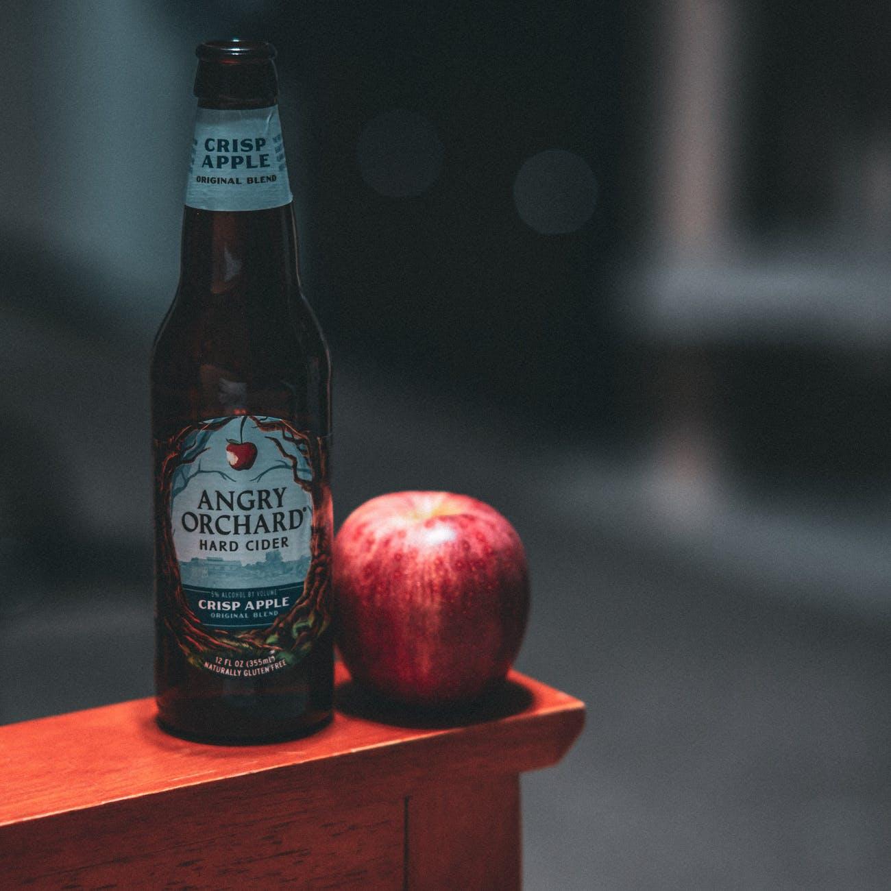 angry orchard hard cider bottle beside red apple fruit